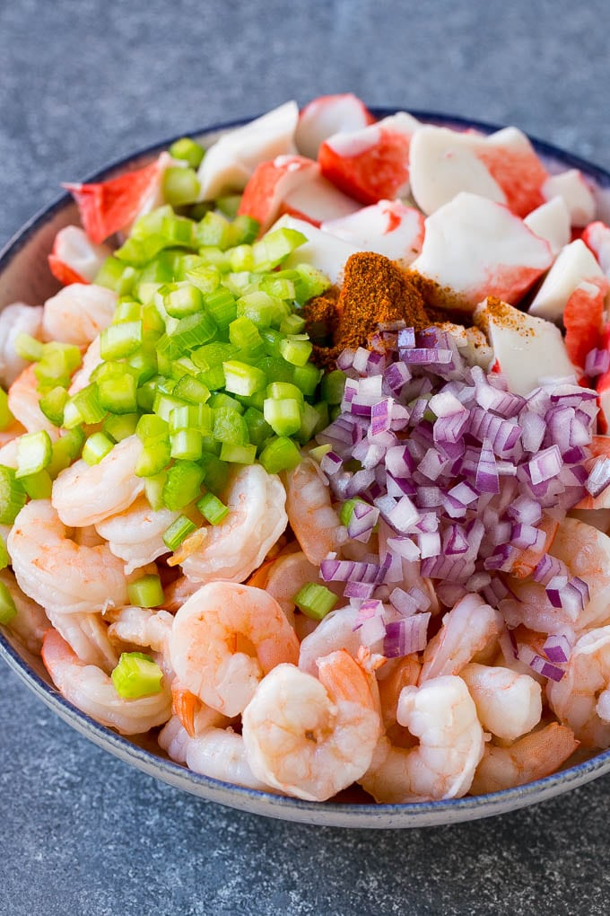 Shrimp, imitation crab, red onion, celery and Old Bay seasoning in a bowl.