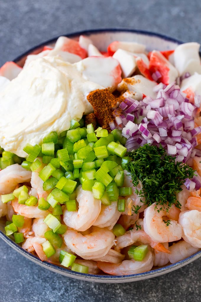 A bowl of shrimp, imitation crab, vegetables, dill and mayonnaise.