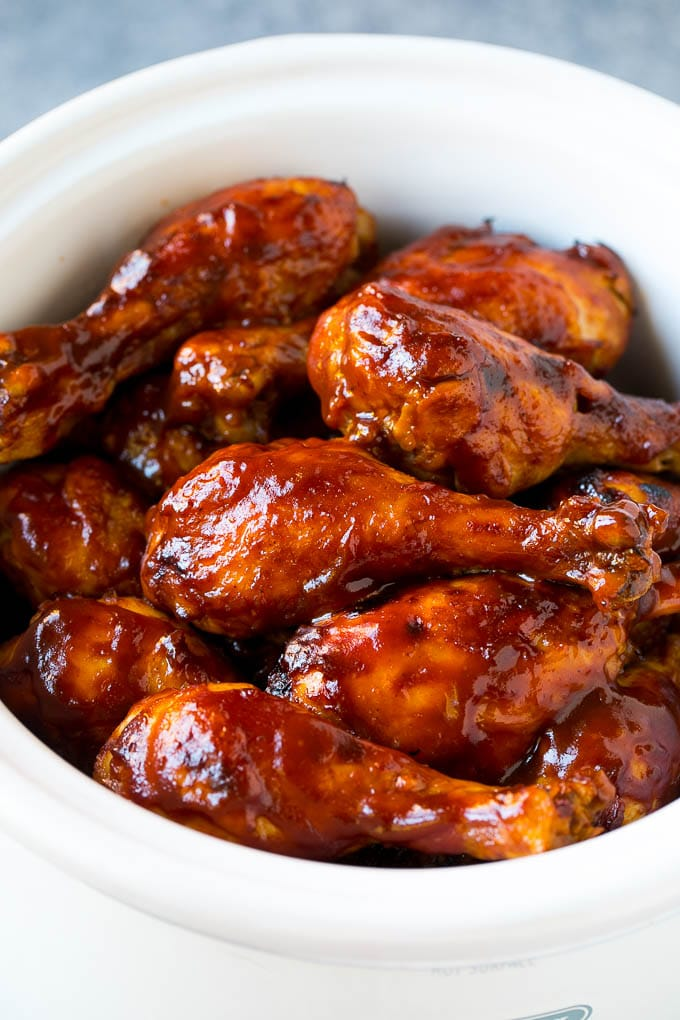 Slow cooker chicken drumsticks coated in BBQ sauce inside a crock pot.