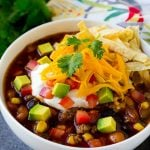 A bowl of taco soup topped with tortilla strips, sour cream, cheese and avocado.