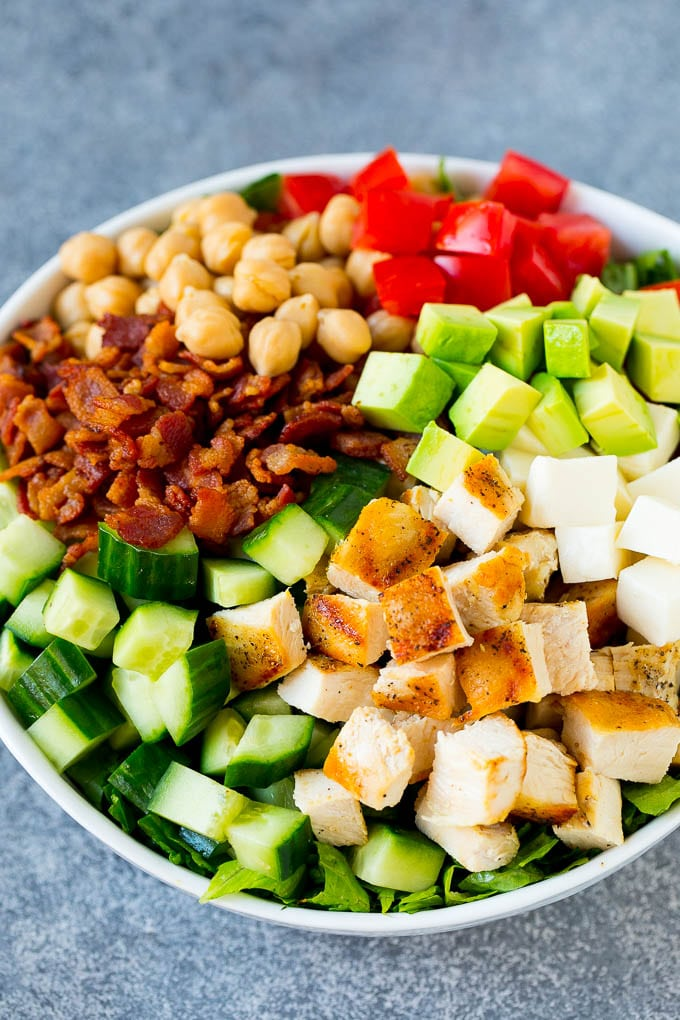 A bowl of lettuce topped with chopped chicken, cucumber, avocado, bacon, chickpeas and tomatoes.