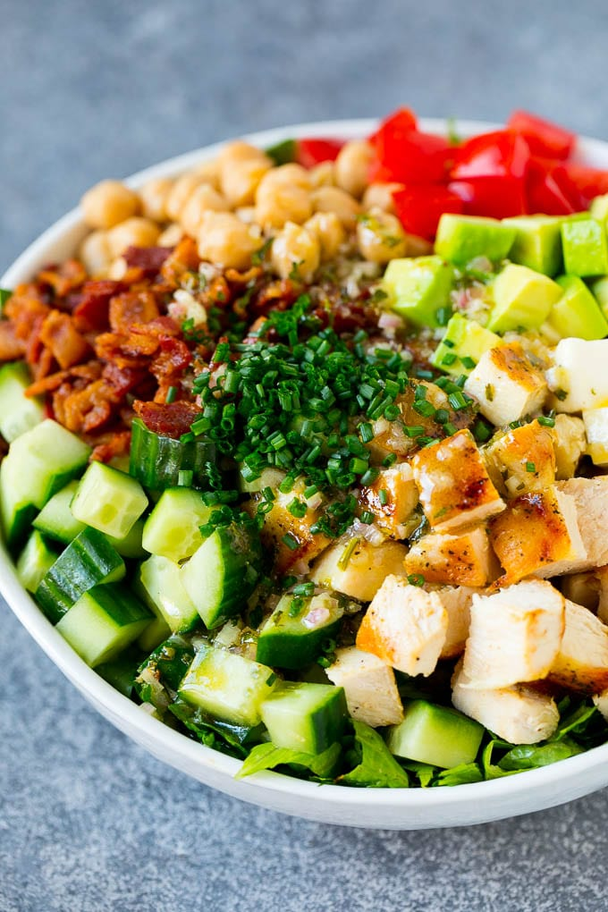 Ingredients for chopped chicken salad in a serving bowl, drizzled with homemade dressing and sprinkled with chives.