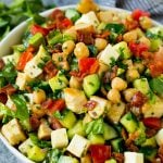 A bowl of chopped salad made with chicken, lettuce, tomato, cucumber, bacon and chickpeas.