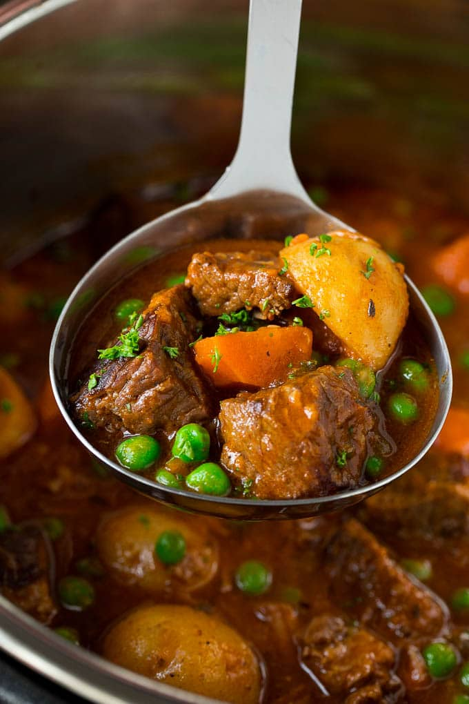 A ladle full of Instant Pot beef stew with chunks of beef, carrots, potatoes and peas.
