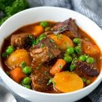 A bowl of Instant Pot beef stew with cubes of meat, potatoes, carrots, onions and peas.