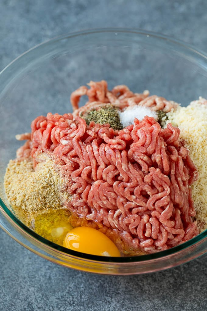 Ground beef, pork, breadcrumbs, parmesan cheese and herbs in a mixing bowl.