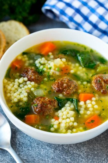 A bowl of Italian wedding soup with meatballs, carrots, spinach and pasta.