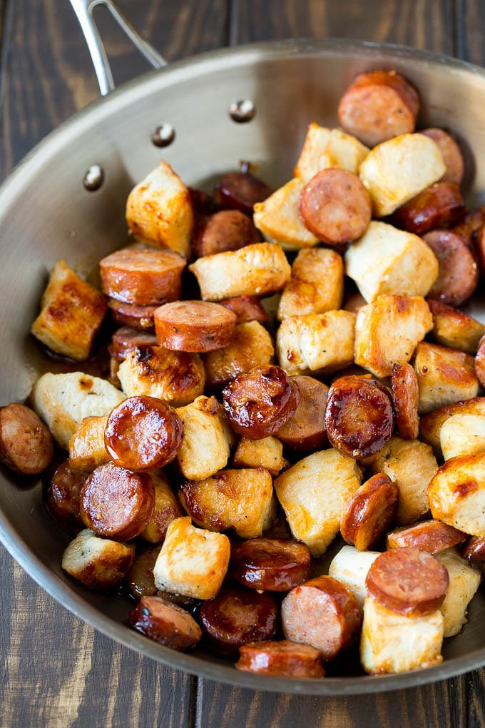 A pan full of sauteed chicken pieces and andouille sausage.