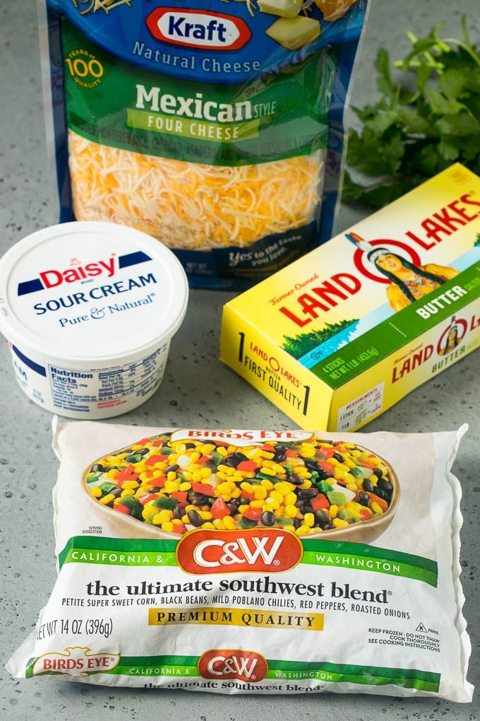 Butter, a bag of frozen vegetables, a bag of shredded cheese and a tub of sour cream.