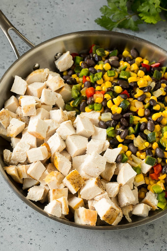 Diced cooked chicken, corn, peppers and black beans in a skillet.