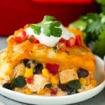 A serving of Mexican casserole made with flour tortillas, cheese, chicken and vegetables.