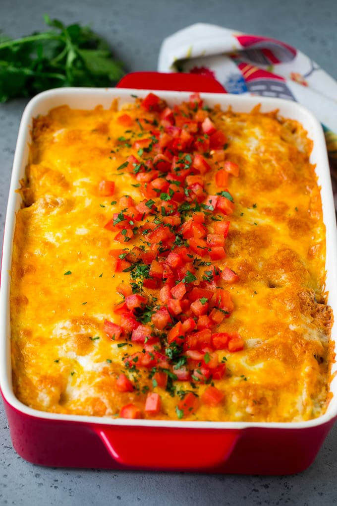 Mexican casserole topped with melted cheese, fresh tomatoes and cilantro.