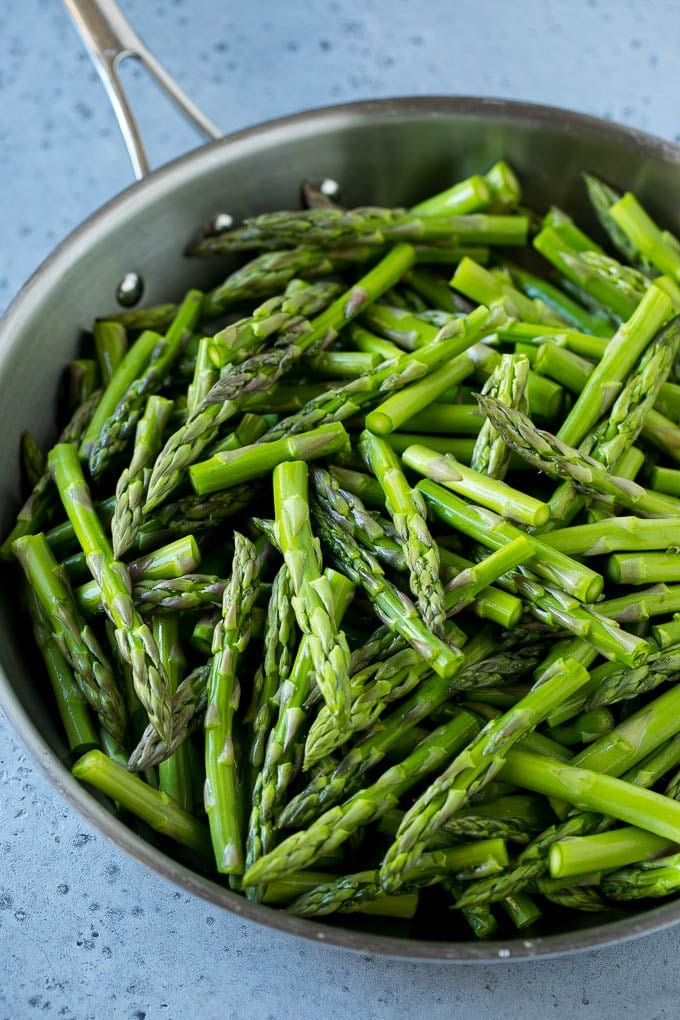 Raw chopped asparagus stalks in a frying pan.