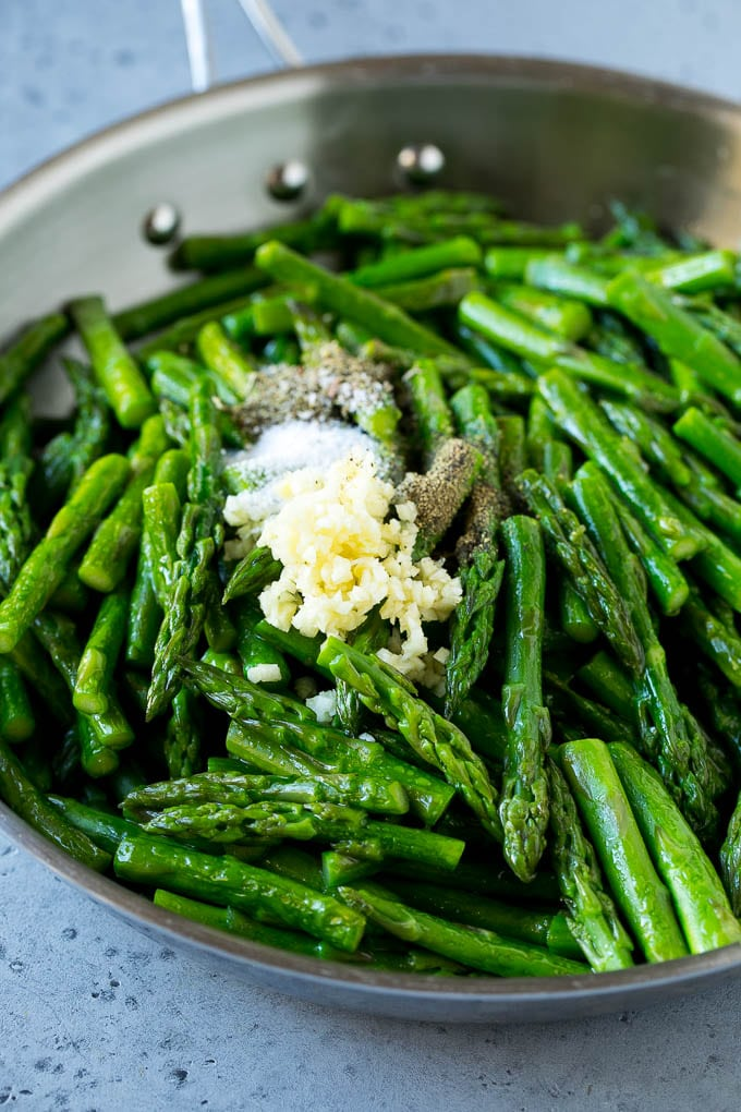 Cooked asparagus stalks in a pan with garlic, herbs and seasonings.