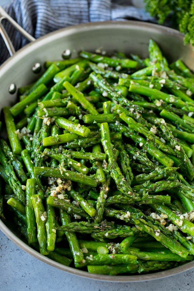 Sauteed asparagus with butter, garlic and herbs in a skillet.