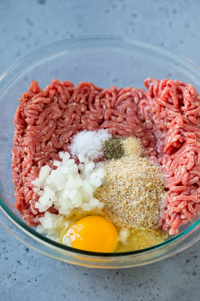 Ground beef, onion, breadcrumbs and seasonings in a bowl.