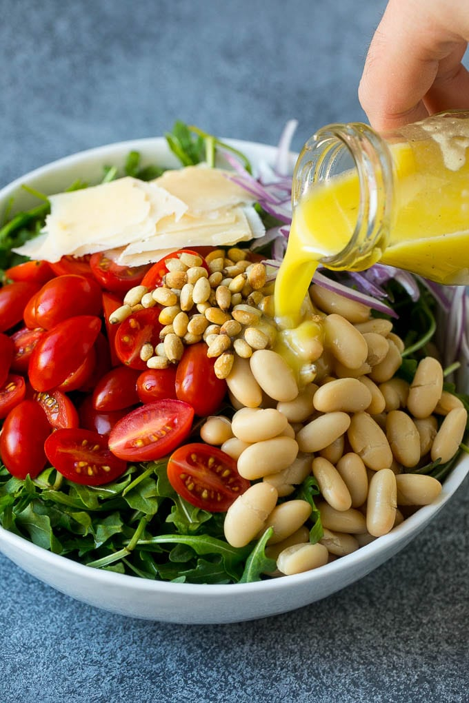 White beans, tomatoes, pine nuts, parmesan and red onion with salad dressing being poured over the top.
