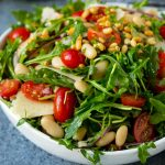 Arugula salad made with white beans, tomatoes, parmesan cheese and pine nuts.