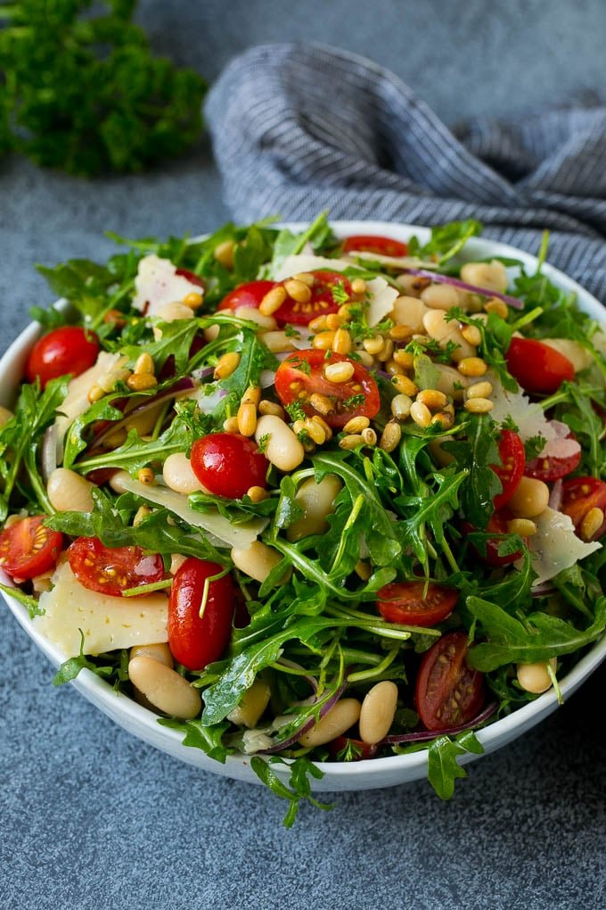A bowl of arugula salad with cherry tomatoes, pine nuts, red onion and shaved cheese.