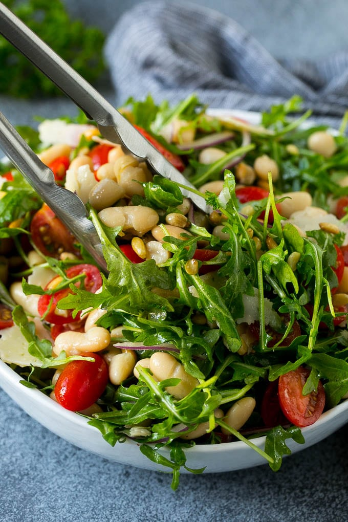 Tongs serving up a portion of arugula salad.