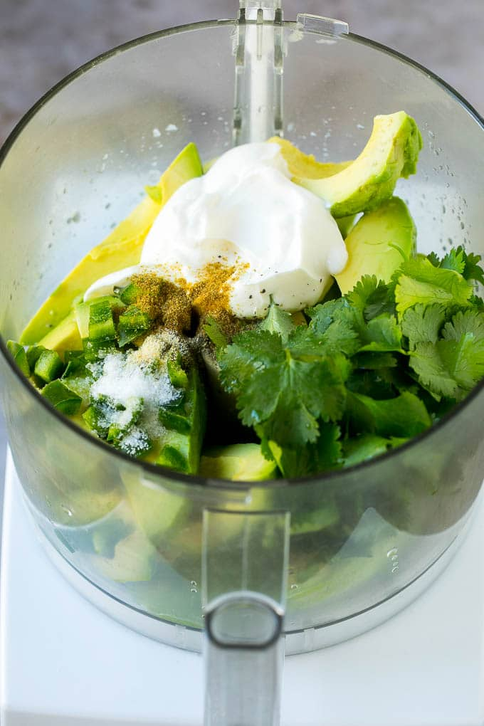 A food processor filled with avocado slices, cilantro, sour cream, lime juice and seasonings.