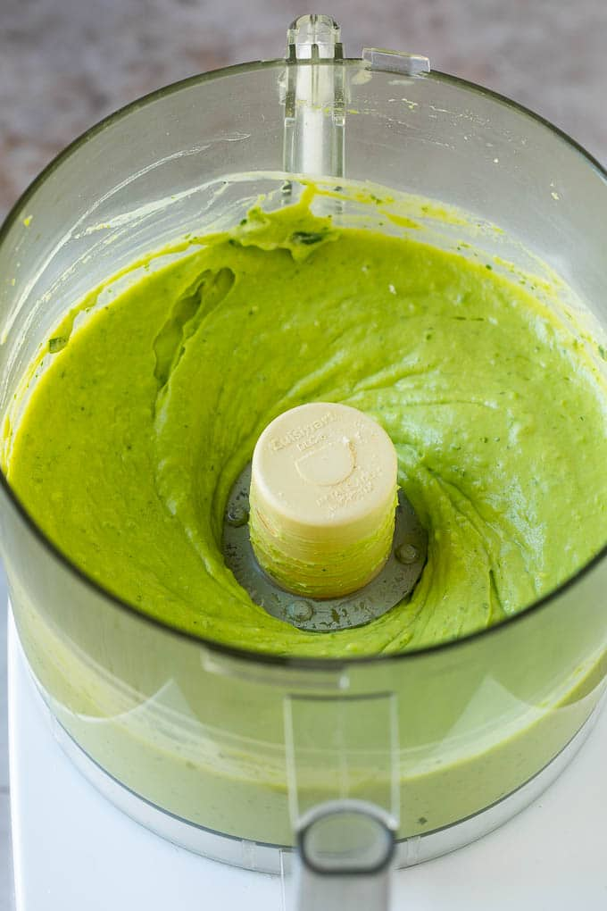 Blended avocado dip in a food processor.