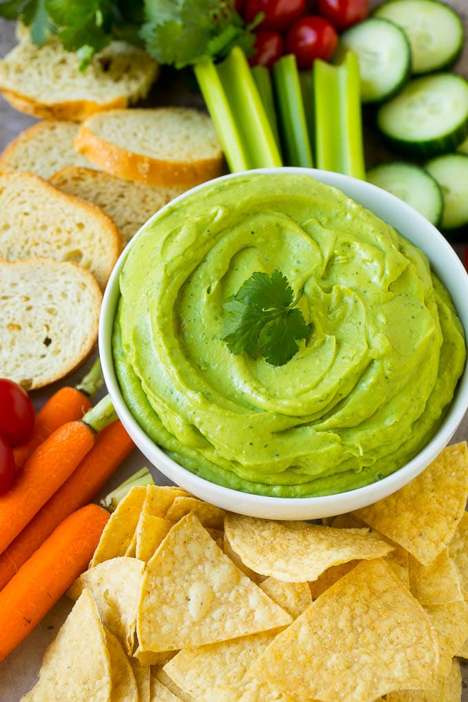 A bowl of avocado dip served with chips, crackers and vegetables.