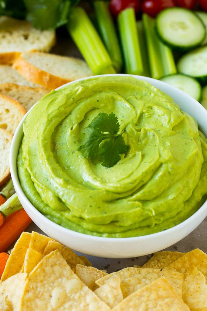 Avocado dip garnished with fresh cilantro and served with tortilla chips and veggies.