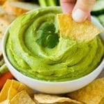 A hand scooping out a portion of avocado dip with a tortilla chip.