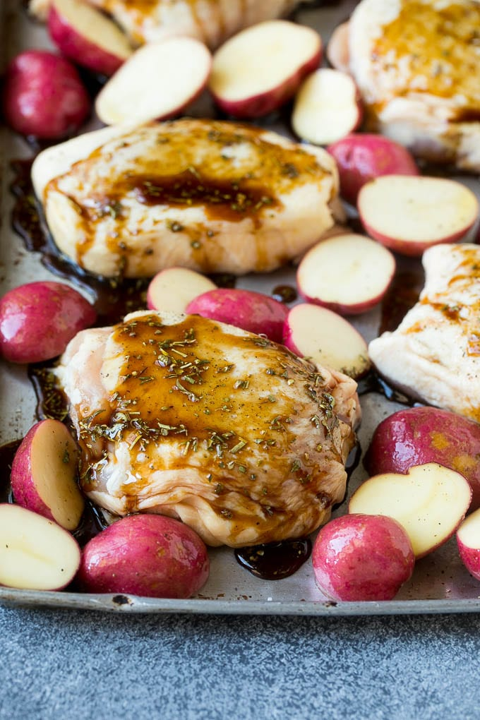 Chicken thighs and potatoes on a sheet pan drizzled with balsamic sauce.