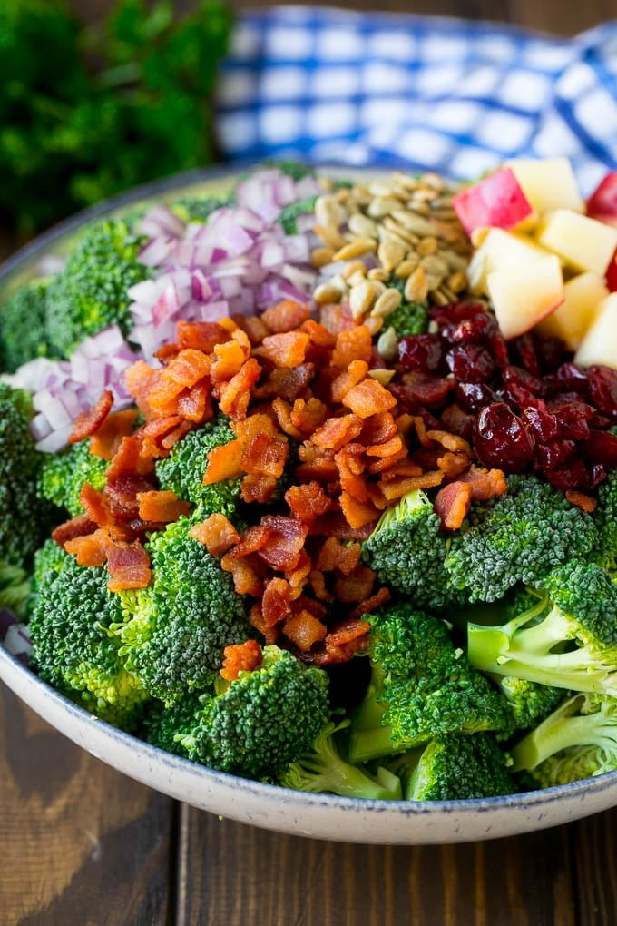 Broccoli florets, bacon, apples, dried cranberries, red onion and sunflower seeds in a bowl.