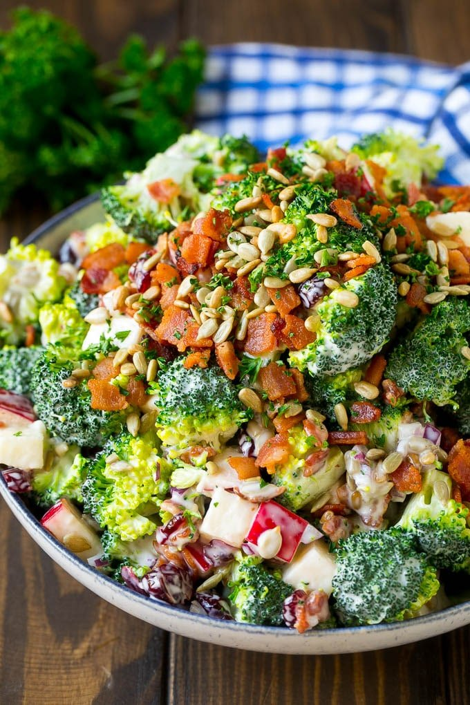 A bowl of broccoli salad made with dried cranberries, apples, bacon and sunflower seeds in a creamy dressing.
