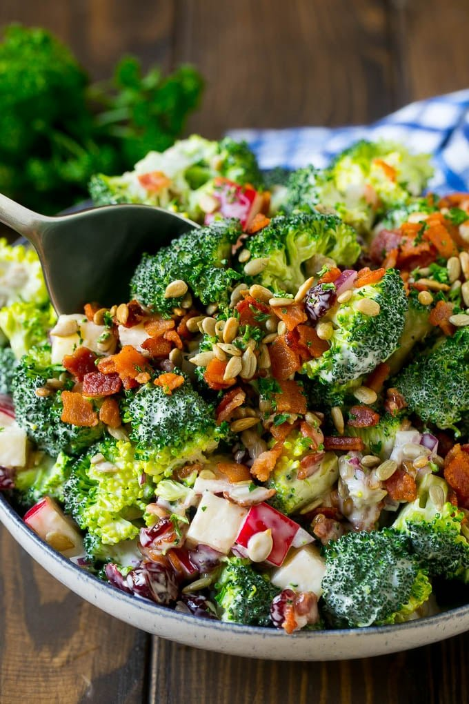A serving spoon in a bowl of bacon broccoli salad.