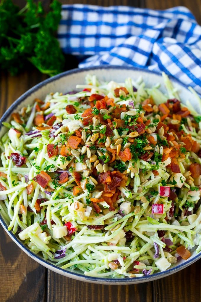 A bowl of broccoli slaw tossed in a creamy dressing with bacon and sunflower seeds.