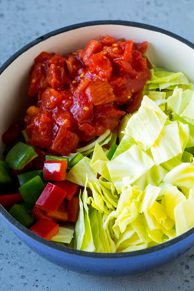 Red and green peppers, diced tomatoes and cabbage in a soup pot.