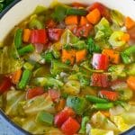 A pot of cabbage soup with carrots, celery, bell peppers and green beans.