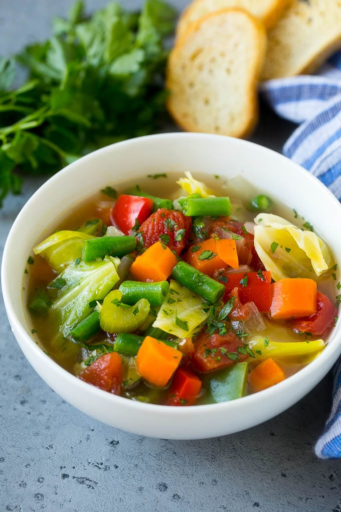 A bowl of cabbage soup with carrots, celery and tomatoes in broth.
