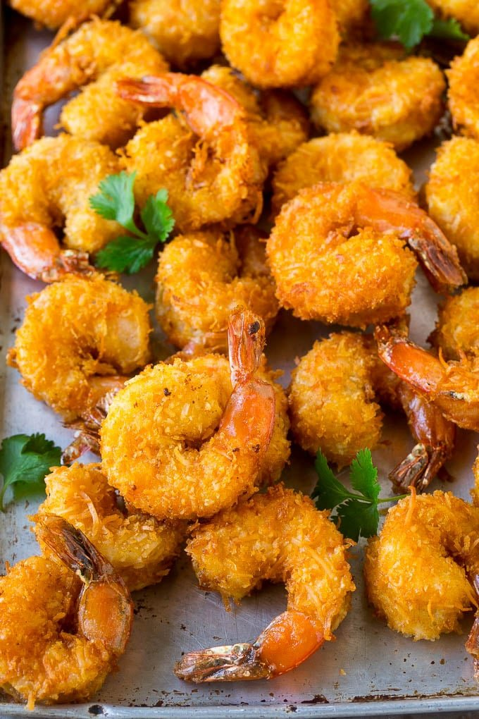A pile of crispy coconut shrimp on a sheet pan with cilantro leaves for garnish.