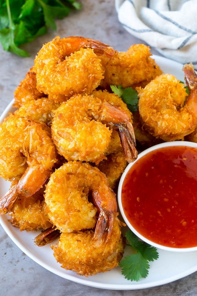 A plate of coconut shrimp with a bowl of sweet chili sauce.