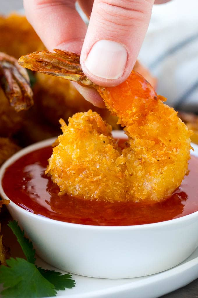 A hand dipping a coconut shrimp into a bowl of sweet chili sauce.