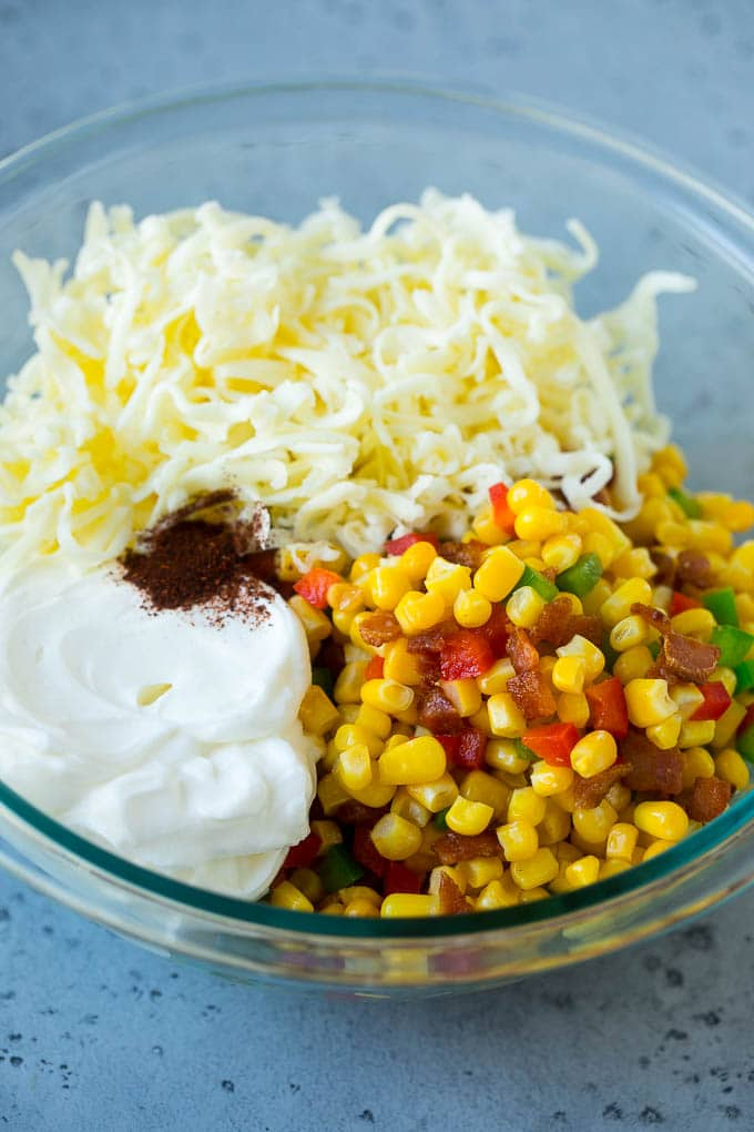 Corn, bacon, bell peppers, sour cream and cheese in a mixing bowl.