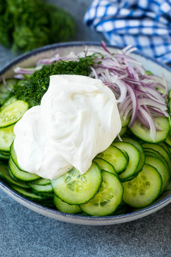 Cucumbers, red onion and dill in a bowl topped with creamy dressing.