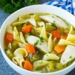 A bowl of crock pot chicken noodle soup with carrots, garnished with parsley.