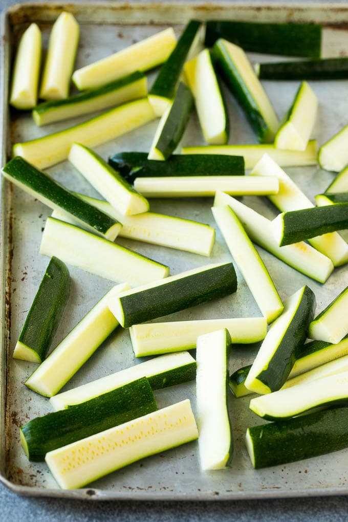 Raw zucchini sticks on a sheet pan.