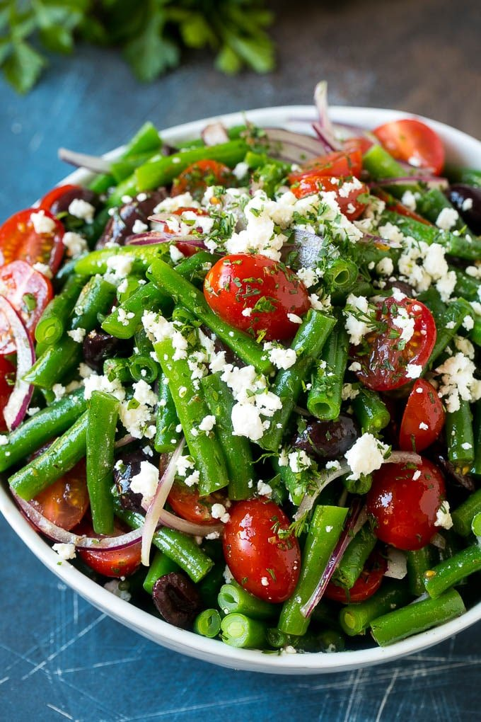 A bowl of green bean salad made with feta cheese, tomatoes, red onion and kalamata olives.