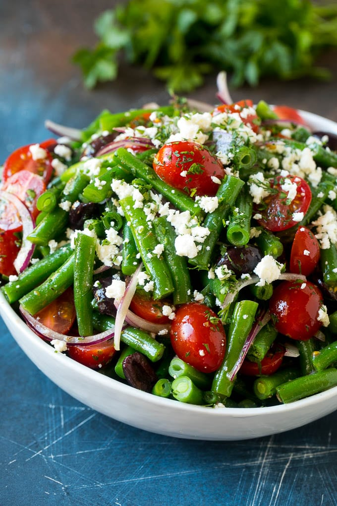 Green bean salad tossed in a vinaigrette and topped with feta cheese and herbs.