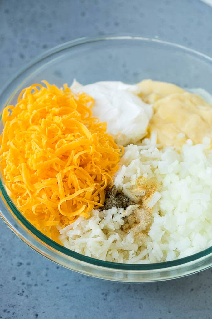 A bowl of hash browns, shredded cheese, cream of chicken soup, sour cream and seasonings.