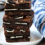 A stack of Oreo brownies filled with sandwich cookies and chocolate chips.