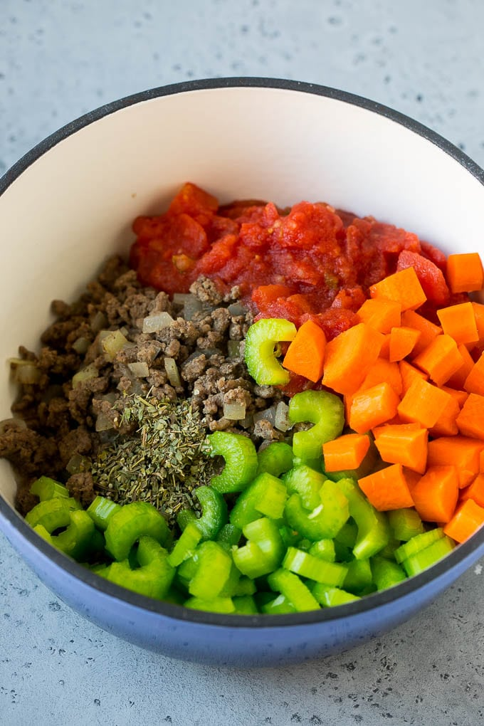 Ground beef, onions, tomatoes, carrots, celery, herbs and spices in a soup pot.