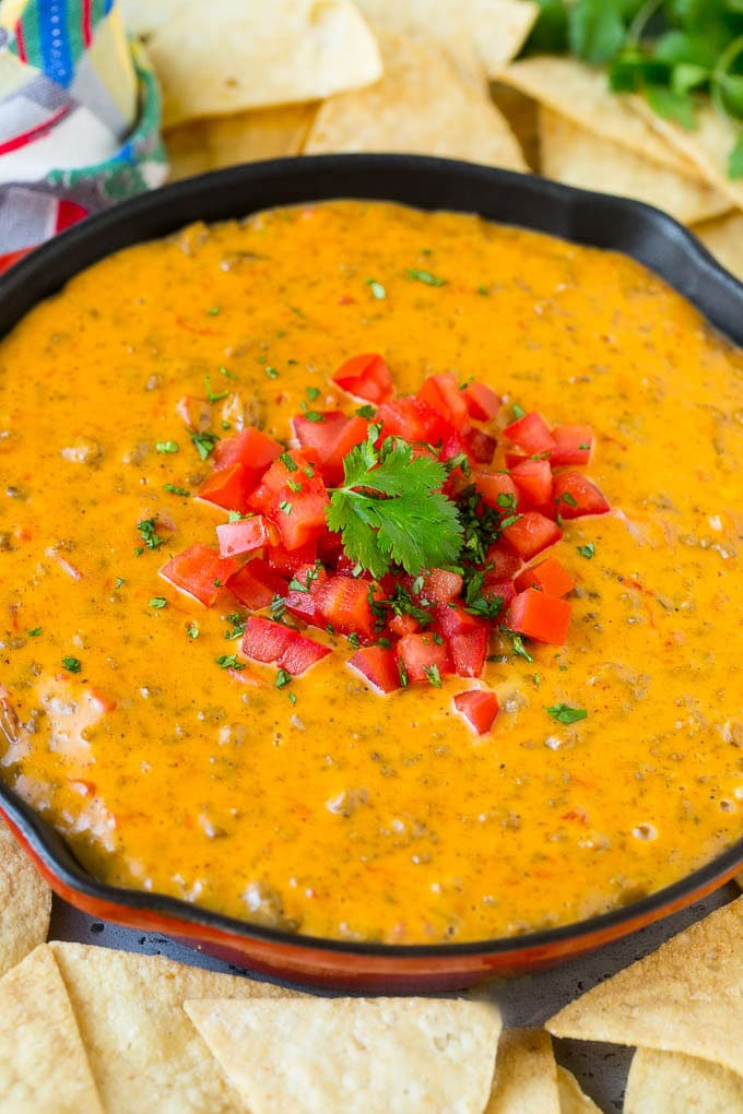 A skillet of Rotel dip topped with fresh tomatoes and cilantro, served with tortilla chips.